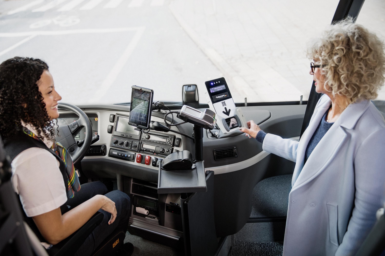 Kvinnlig resenär skannar biljetten i bussen